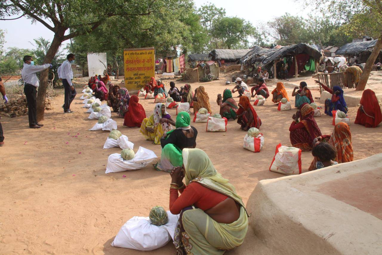 Villagers receive their share of vegetables and food grains