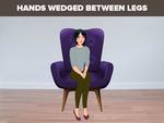 Hands wedged between legs