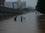 People walk through waist-deep water