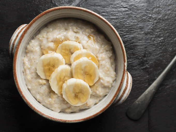 a bowl of oatmeal topped with a few slices of banana, as the #3 food to help prevent/ manage hypertension/ high blood pressure