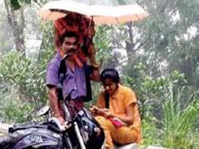 Karnataka girl studies by roadside, dad protects her from rain