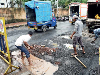 Workers fill potholes with debris, bricks