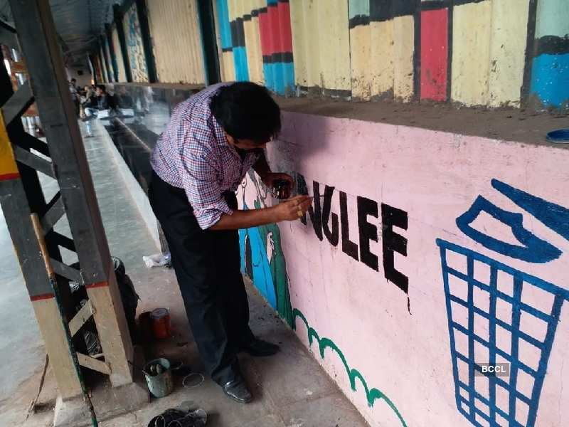 NK Sinha painting messages on the station wall