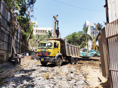 Trucks bearing MMRCL signage dump construction debris in Wadala
