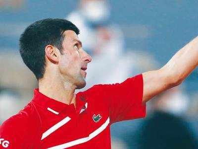 Djokovic triumphs but loses cool in rain-marred match