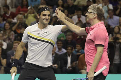 What is Bill Gates doing with Roger Federer on a tennis court?