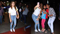 Sara Ali Khan beats jet lag with a dose of laughter, poses with little fans at the airport as she rocks a white crop top and denim look