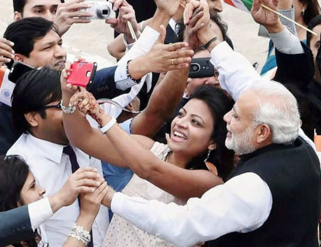 A woman takes selfie with Prime Minister Narendra Modi at Seoul Air Base in Seoul, South Korea. (PTI File Photo)