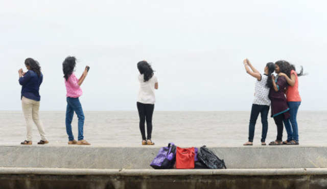 Youngsters take 'selfies' on Marine Drive promenade in Mumbai. (AFP photo)