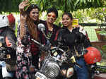 A lady biker poses with her friends