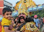 An artist dressed as Ravan poses with a kid