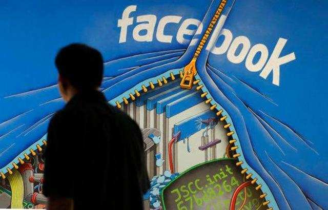 FILE - In this June 11, 2014, file photo, a man walks past a mural in an office on the Facebook campus in Menlo Park, Calif. Facebook is investing $750 million over the next five years to build a huge data center outside of Atlanta. Georgia Gov. Nathan Deal held a news conference Wednesday, March 7, 2018, to announce that the social media giant's 9th U.S. data center will be built in Newton County.Photo/Jeff Chiu, File)