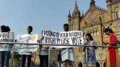 Students hold aloft banners urging citizens to vote, at Selfie Point, CSMT
