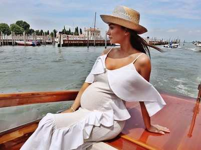 Amy travels the world flaunting her baby bump