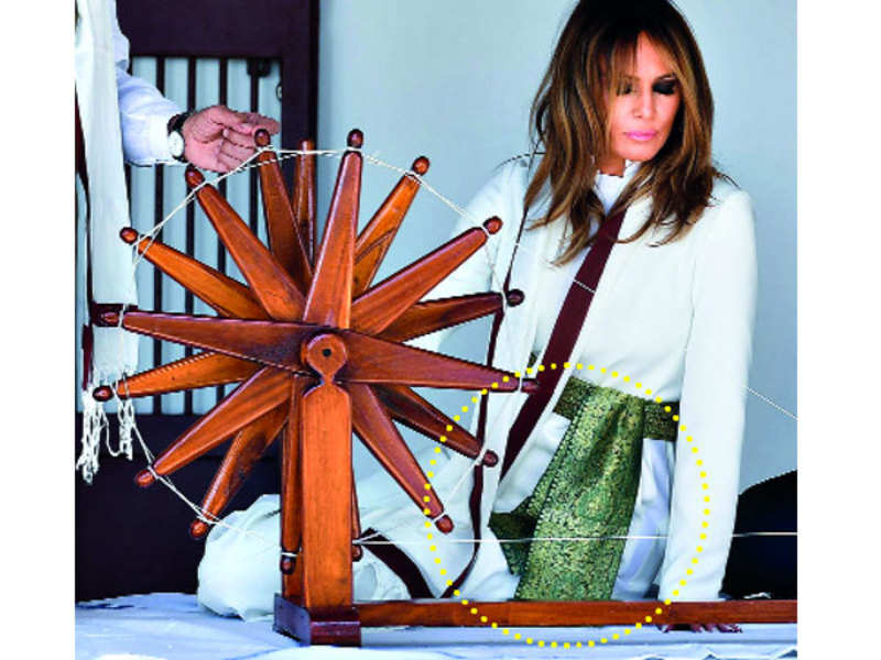 Giving a touch of desi to her white jumpsuit, Melania Trump had a green Banarasi sash tied around her waist as she descended from Air Force One with POTUS Donald Trump in Ahmedabad on Monday