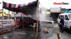Corporation workers spray disinfectant on barricades, police tents and containment areas