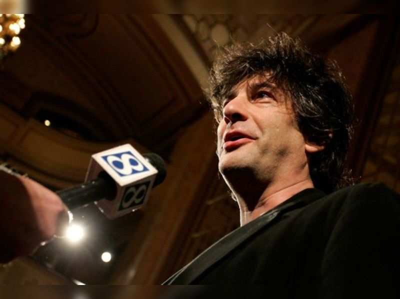 """British author Neil Gaiman talks to a reporter as he arrives at the premiere of the animated movie """"Coraline"""" in Portland, Oregon February 5, 2009. REUTERS/Richard Clement (UNITED STATES) - GM1E52610DD01/File Photo"""