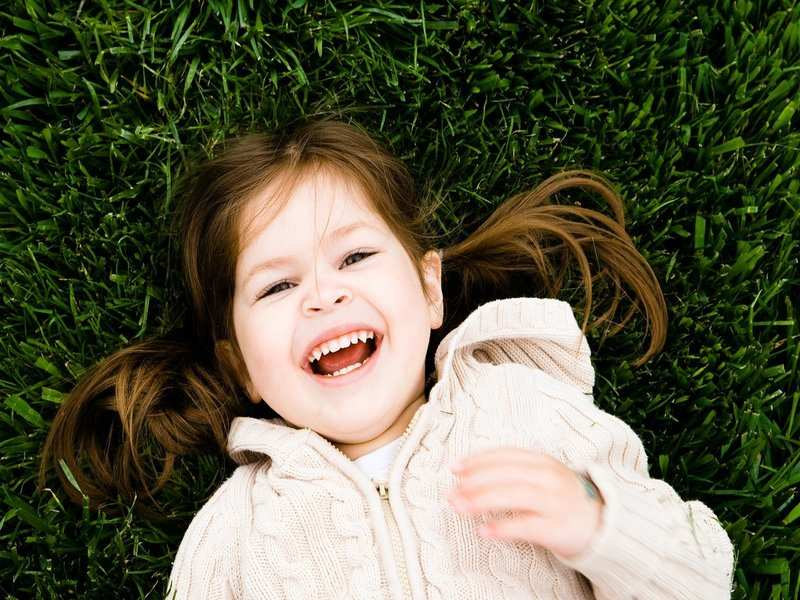 A little girl smiling while lying on the grass
