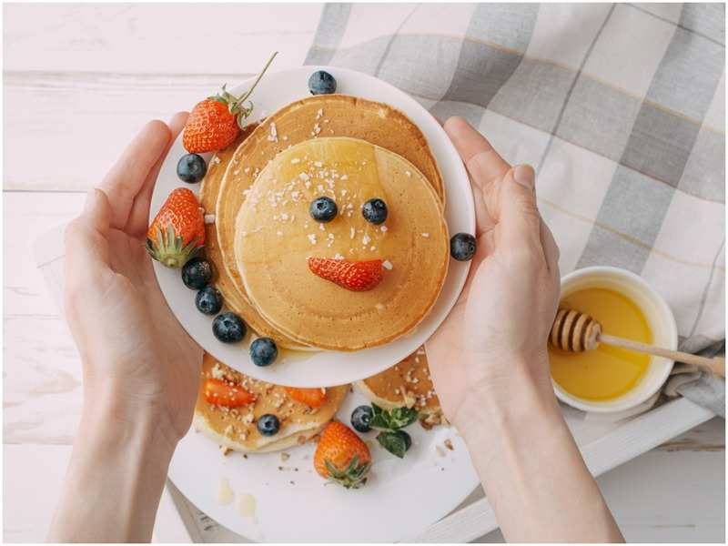 This pancake has berries and honey in the shape of a smiling face