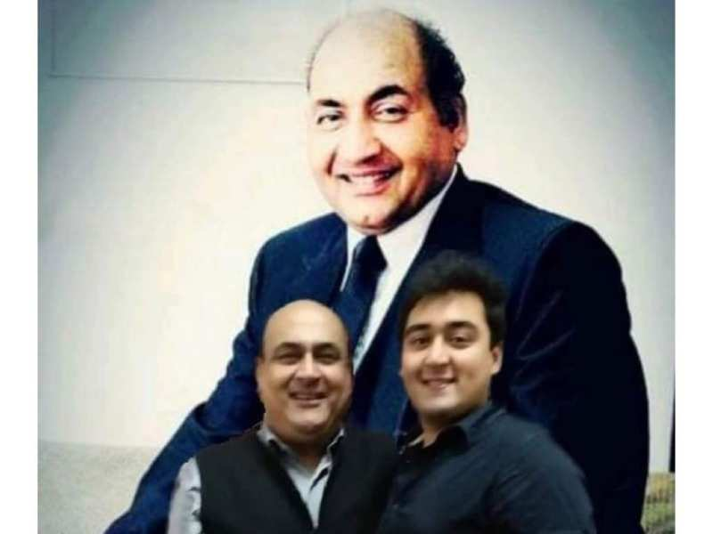 Mohammed Rafi's son Shahid Rafi and grandson Fuzail Rafi pose for a shot in front of the late singer's portrait