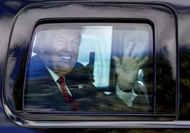 Former US President Donald Trump waves to supporters as his motorcade drives through West Palm Beach, Florida, on his way to his Mar-a-Lago club in Palm Beach after arriving from Washington aboard Air Force One on 20 January 2021.