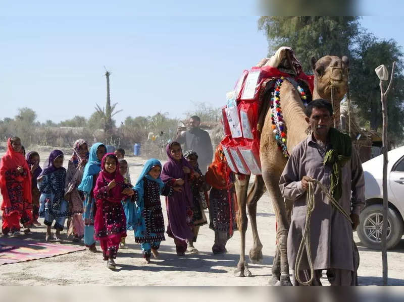 Children react as Roshan the camel carries books in Mand, Pakistan April 11, 2021.ATTENTION EDITORS - THIS IMAGE HAS BEEN SUPPLIED BY A THIRD PARTY. NO RESALES. NO ARCHIVES.
