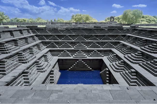 Queen's bath in Hampi with symmetric steps in stonework–stepwell